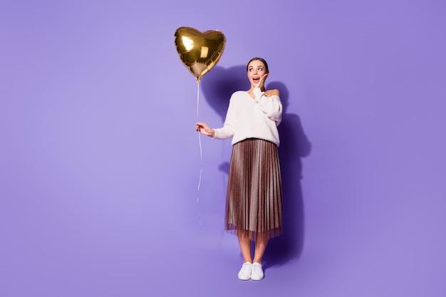Милая привлекательная изумленная девушка держит в руке гелиевый шар