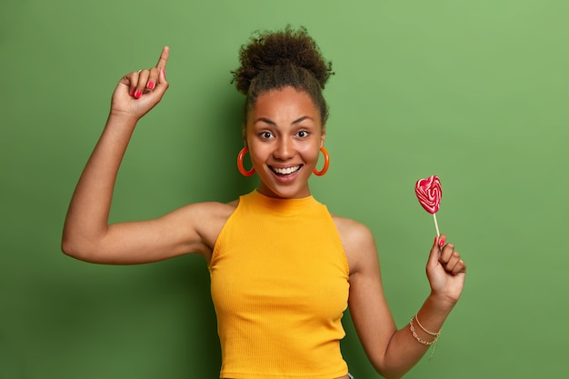 Nice attractive carefree girlfriend dances happily with heart shaped lollipop, has fun indoor, has sweet tooth and good mood after eating yummy candy, moves with joy over vivid green wall