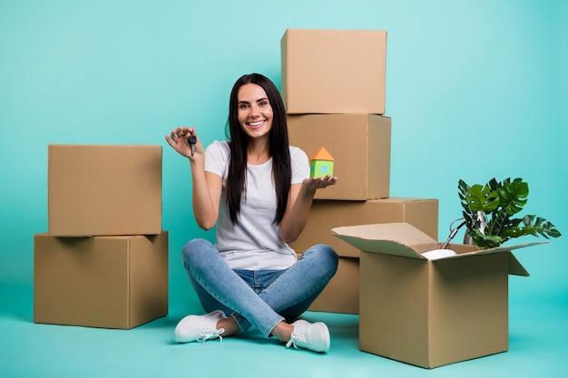 Симпатичная привлекательная жизнерадостная девушка, сидящая в позе лотоса с кучей коробок, держащая в руках фигуру дома