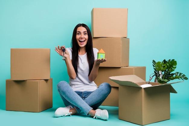 Симпатичная привлекательная, восторженная жизнерадостная девушка сидит в позе лотоса, держа в руке фигуру дома