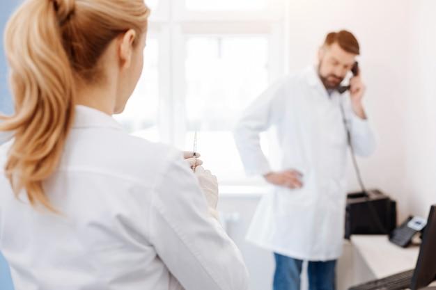 彼女の同僚を見て、注射をする準備ができている間注射器を持っている素敵な魅力的な専門医