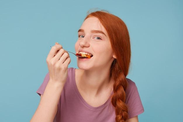 Una bella e attraente donna dai capelli rossi che prova ad assaggiare mangia qualcosa di delizioso