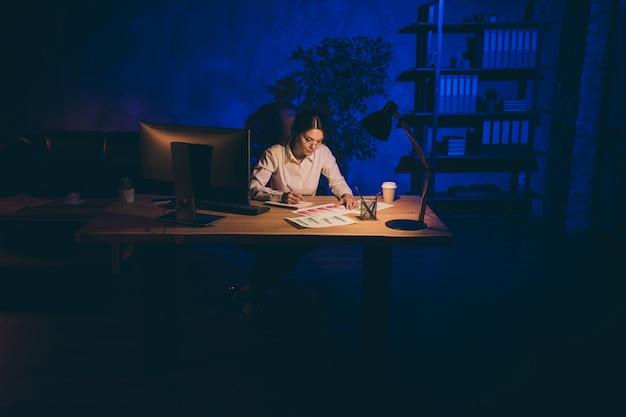 Симпатичная привлекательная стильная сосредоточенная одинокая одинокая женщина, трудолюбивый топ-менеджер, аналитик, маркетолог, финансист, анализирует данные, готовит отчет в одиночестве ночью, темное рабочее место, станция, в помещении