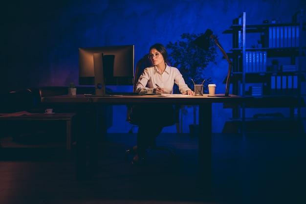 素敵な魅力的なスタイリッシュな孤独な独身女性トップエグゼクティブマネージャーアナリストマーケターフィナンシェスタートアップの結果を分析する夜遅くに一人でレポートを準備する真夜中の暗い職場の駅