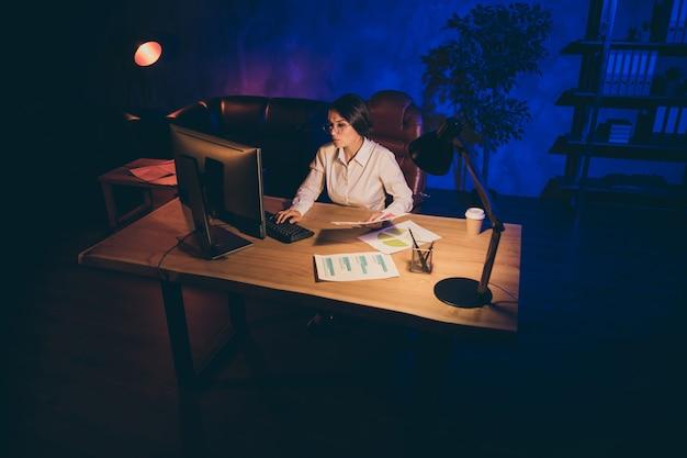 Симпатичная привлекательная стильная одинокая одинокая женщина, топ-менеджер, маркетолог, финансист, анализирует финансовый результат стартапа, готовит ежедневный отчет ночью темный индустриальный стиль интерьера рабочее место