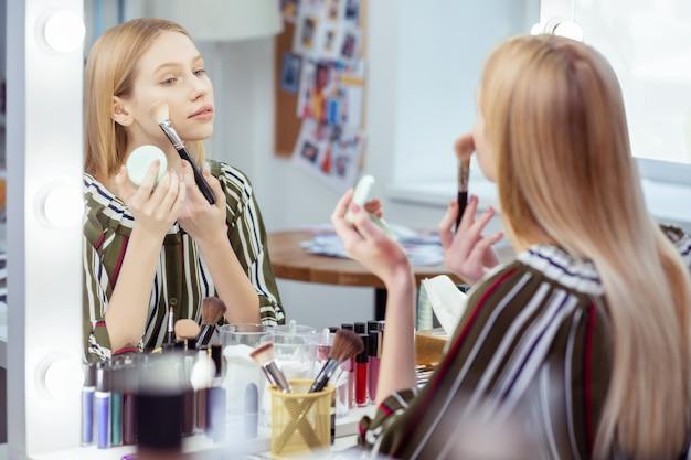 化粧をしながら彼女の反射を見ている素敵な魅力的な女性