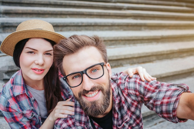 Nice bearded man and positive young woman sit on stairs and pose. he holds camera. they look at it. tourists have rest.