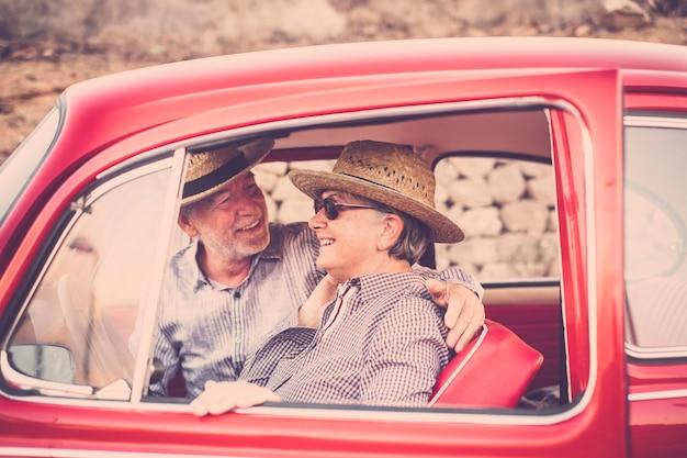 古い赤いヴィンテージカーの中にいる年配の大人の素敵な美しいカップルは、屋外旅行のレジャー活動を楽しんで一緒に滞在します。結婚して永遠に一緒に暮らす。ハッピンと旅行のコンセプト