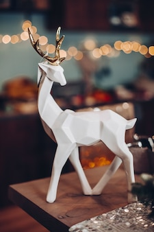 Nice beautiful deer figurine on a background of lights. new year eve concept