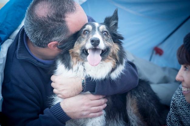 Милая красивая собака бордер-колли действительно счастливая и радостная концепция обняла своего хозяина кавказского мужчины среднего возраста. женщина посмотрите их. семейная альтернативная концепция