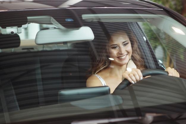長い巻き毛の素敵な美しい女の子が座って、黒い車の中でハンドルを握っています。ディーラーで車を買うだけです。車両購入のコンセプト。フロントガラスを通して見る。