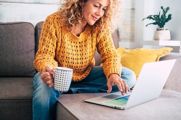 ノートブックで金髪の巻き毛の仕事をしている素敵な美しい女性が自宅のソファに座っています-サイバーマンデーの販売のためにラインショップをチェックしてください-代替オフィスフリーランスのテクノロジー女性のコンセプト