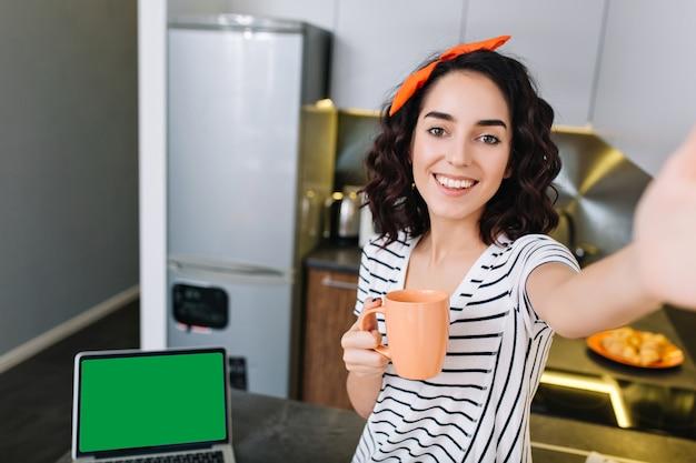 Красивый красивый селфи-портрет удивительной радостной счастливой женщины с вырезанными вьющимися волосами брюнетки, охлаждая на кухне в современной квартире. веселимся, пьем чай