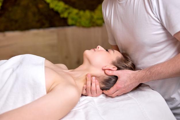 Nice beautiful woman lying on massage table and enjoying massage by professional