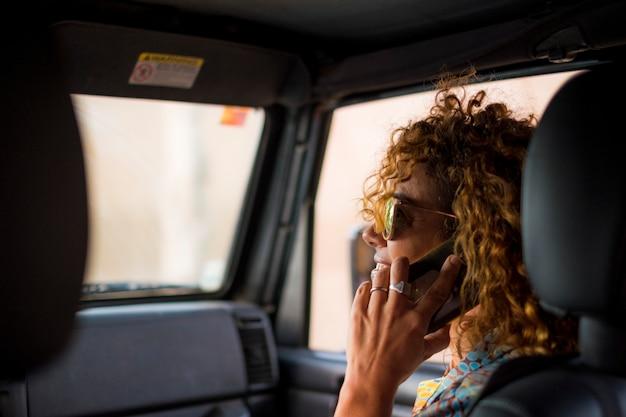 素敵な美しい若い女性が笑顔で、旅行中に車内の画面に触れる携帯電話を使用する
