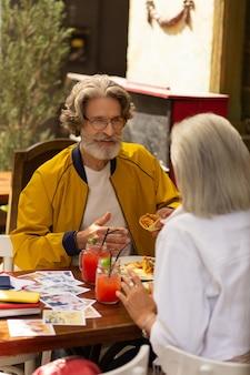 좋은 하루의 시작. 수염을 기른 행복한 남자는 아내와 함께 거리 카페에 앉아 멕시코 음식을 먹고 있습니다.