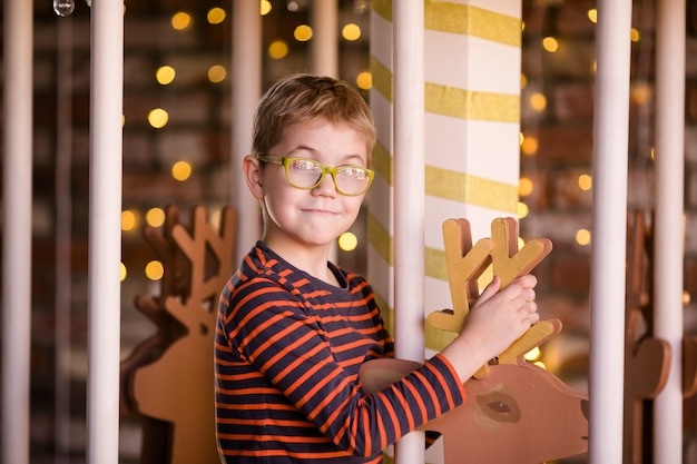 Nice blonde boy with glasses on the new year carousel with wooden deer and bright lights