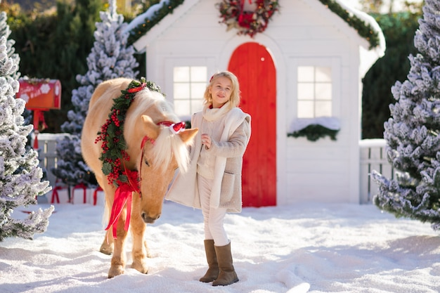 Nice blonde curly child and adorable pony near the small wooden house and snow-covered trees.