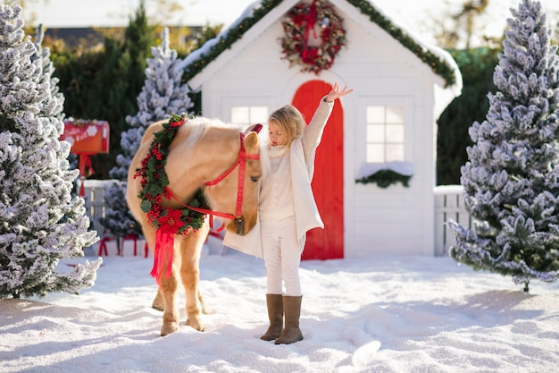 Nice blonde curly child and adorable pony with festive wreath near the small wooden house and snow-covered trees.