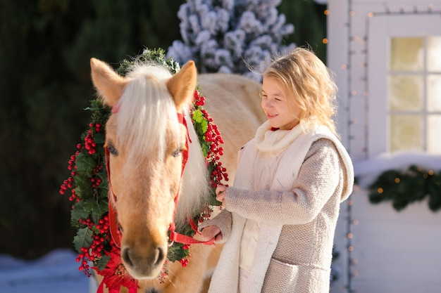 Nice blonde curly child and adorable pony with festive wreath near the small wooden house