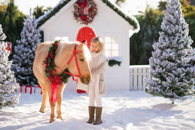 Nice blonde curly child caresses adorable pony with festive wreath near the small wooden house