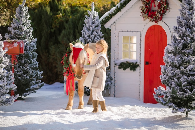 Nice blonde curly girl and adorable pony with festive wreath near the small house