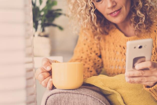 家でお茶やコーヒーを飲み、携帯電話を使ってインターネット技術を使って、レジャーやビジネスの活動にウェブ検索を行う、素敵な金髪の巻き毛の中年女性