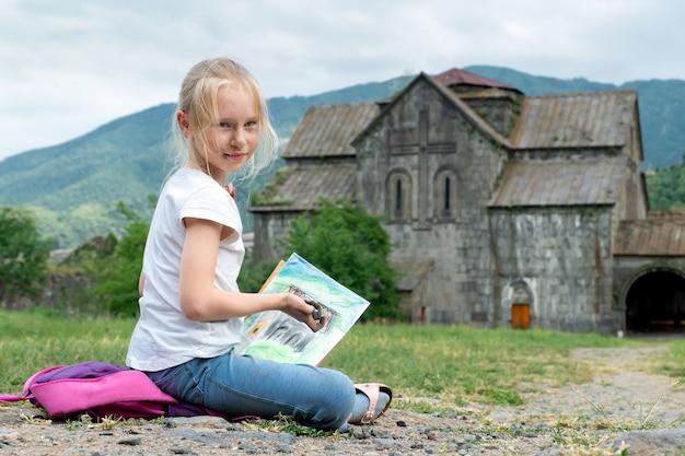 Симпатичная блондинка-школьница сидит на земле перед древним монастырем с испачканным краской лицом во время урока рисования и смотрит в камеру