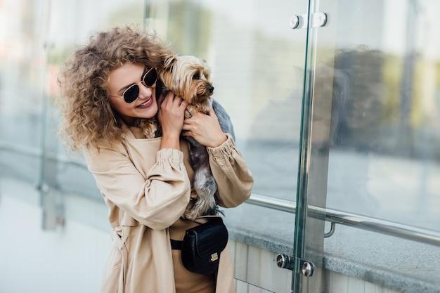 Bella donna bionda con il suo cane in una città, concetto di amore per gli animali domestici. amicizia umana e animale. stile di vita.