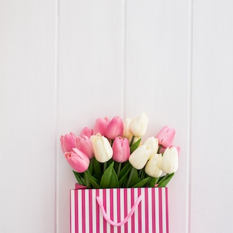 Nice bouquet of tulips inside a white and pink bag on a white wooden background