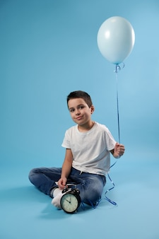 Nice boy smiles sitting near an alarm clock on a blue surface and holding a blue balloon