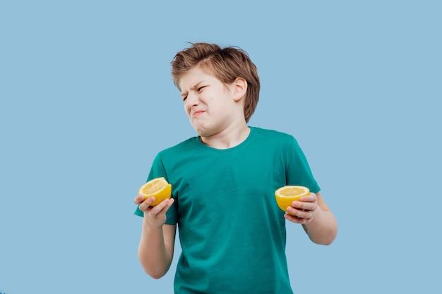 Приятный мальчик попробовать свежий лимон, кислый вкус, сделать гримасу,