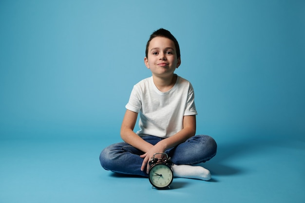 Nice boy wearing white t-shirt and jeans sitting on a blue surface with copy space behind an alarm clock