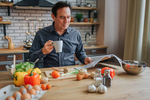 Nice buinessman sit at table in kitchen and read journal. he hold white cup. man look concentrated. spices and vegetables lying on table.