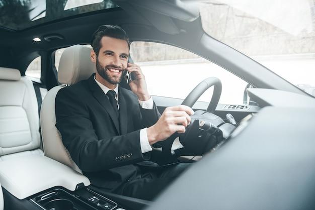 Хороший деловой разговор. красивый молодой бизнесмен разговаривает по своему смартфону и улыбается, сидя на переднем сиденье
