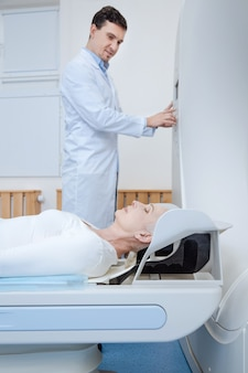 Nice calm elderly woman lying on an examination table and closing her eyes while being examined in the lab
