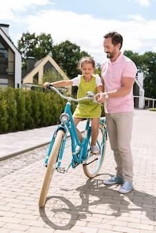 자전거를 타는 것을 돕는 동안 딸 근처에 서있는 좋은 돌보는 아버지