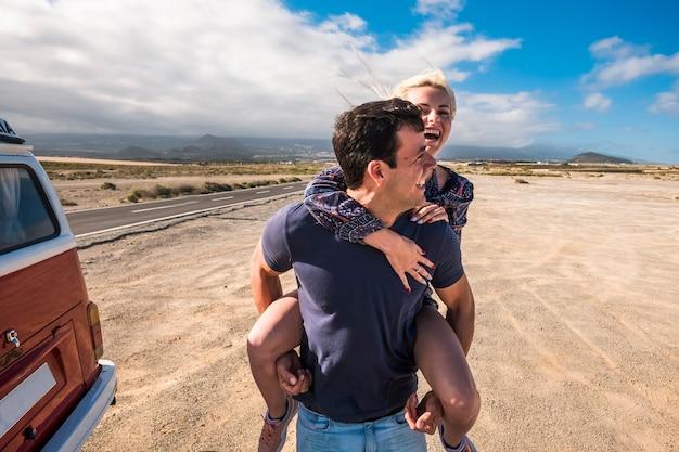 愛の素敵な白人の美しいモデルのカップルは、古い代替キャンピングカーとの長い旅行の休暇で砂漠を横断する長い道の近くで屋外のレジャー活動で一緒に遊んで滞在します