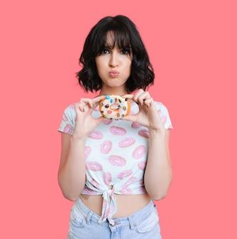 화려한 도넛을 잡고 강조하는 멋진 백인 갈색 머리 소녀는 산호 빈 공간에 뭔가를 홍보하고 있습니다