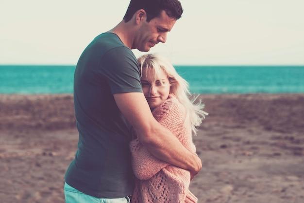 Хорошая кавказская пара в отпуске на открытом воздухе. наслаждайтесь и улыбайтесь в любви вместе, играя и обнимаясь, полные прекрасных мыслей. пляжное место и цветной горизонт океана
