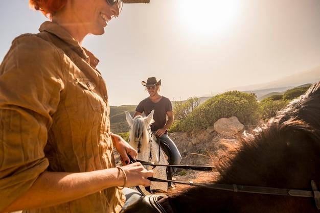 素敵な白人のカウボーイ カップルが風 ladscape 風光明媚な場所で馬に乗る