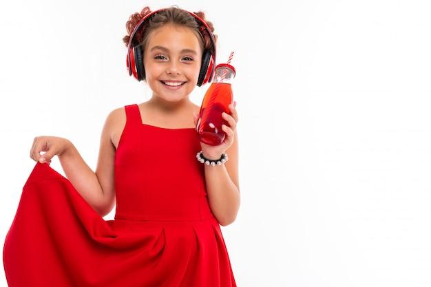 Милая кавказская девушка в красном платье с большими наушниками слушает музыку и пьет сок, изолированный на белой стене