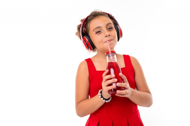 Nice caucasian girl in red dress with big earphones listen to music and drinks juice isolated on white wall