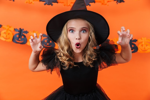 Nice caucasian woman in black halloween costume scratching and looking at camera isolated over orange pumpkin wall