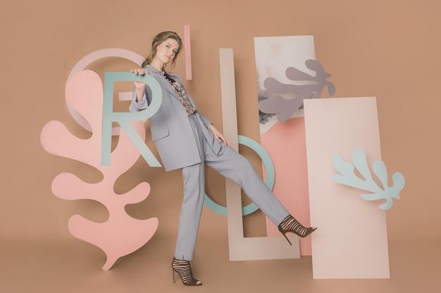 ベージュの背景に奇妙なインスタレーションでスタイリッシュな青い衣装でポーズをとる素敵な白人女性