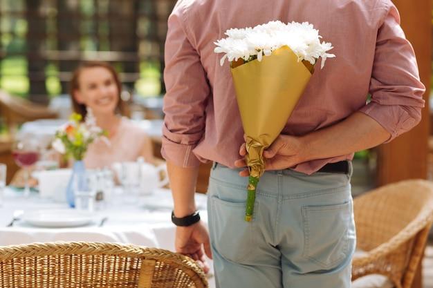 素敵なカモミール。彼の誕生日のガールフレンドにカモミールを提示しながら心配を感じている愛情のある思いやりのある男