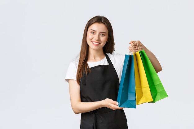 Симпатичная очаровательная улыбающаяся кассирша в черном фартуке раздает покупателям сумки с купленными товарами и желает хорошего дня. продавщица работает над счетчиком, стоя на белом фоне.