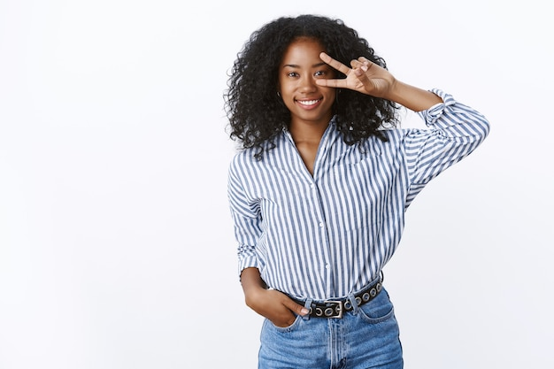 Nice charming smiling happy young dark-skinned girl curly-haired wearing trendy striped blouse jeans showing disco peace victory sign on eye grinning joyfully posing cute shot white wall