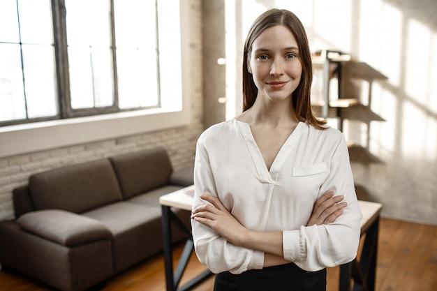 素敵な陽気な実業家がカメラにポーズします。彼女は部屋に一人で立ちます。空の。明け。