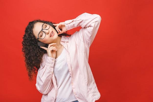 音楽を聴く、踊る素敵な陽気な縮れ毛のブルネットの学生の女の子